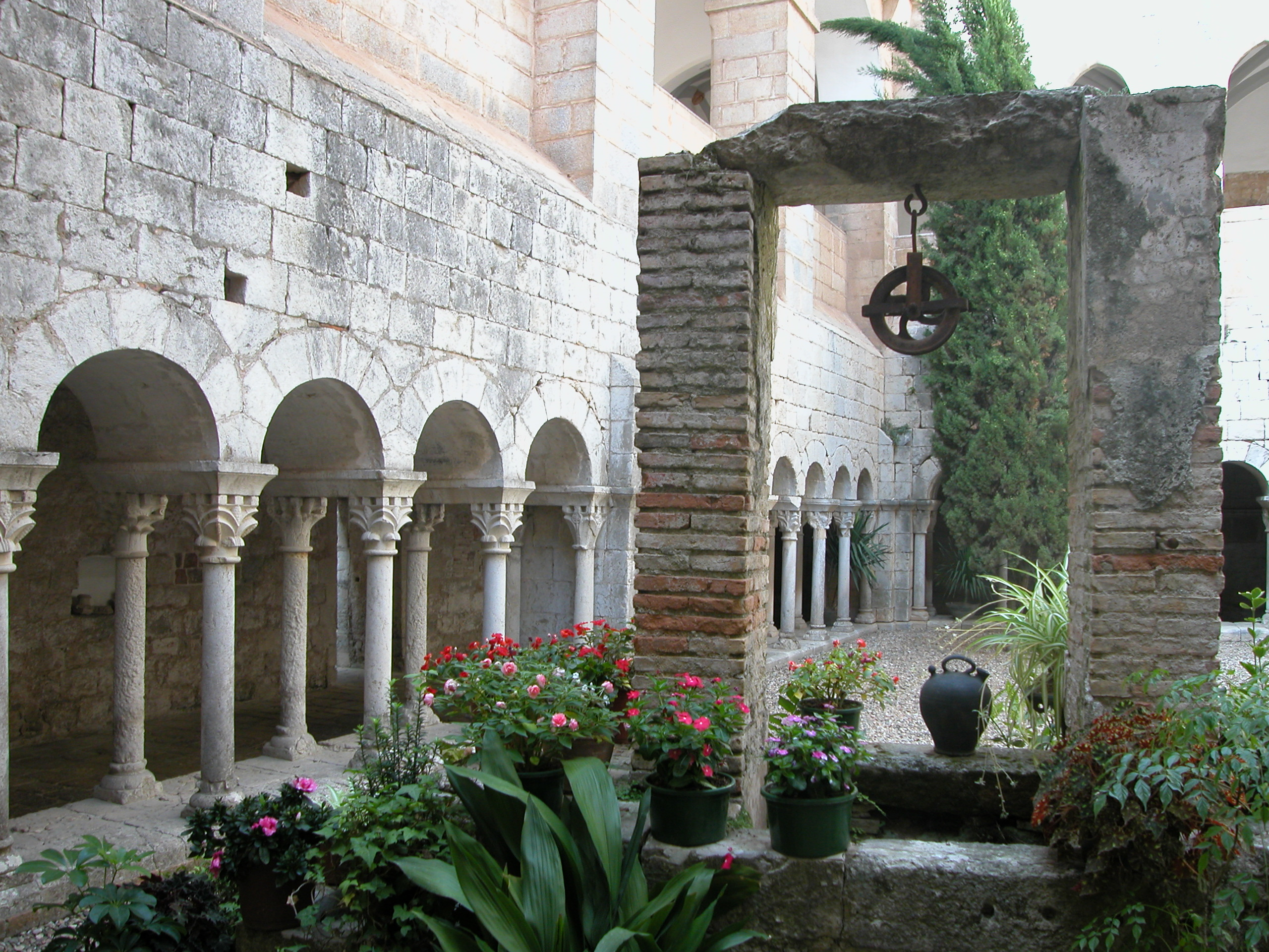 A l'entrada de Girona a les Gavarres trobem un dels monestirs benedictincs més antics de Catalunya. La imatge ens mostra el claustre del cenobi, amb la seva doble arcuació de columnes amb els capitells amb motius vegetals. En el primer terme hi ha el pou d'aigua amb la politja i un càntir.