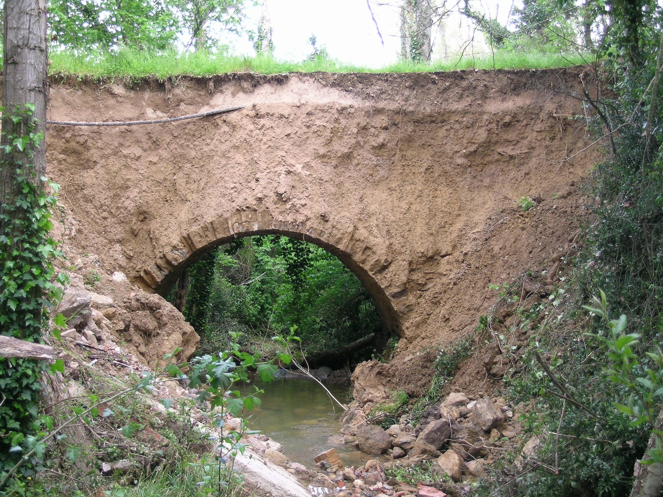 Pont enimg del bosc per anar a la font de les Mallenes. Ha perdut el frontal construït i es veu la volta i el reompliment de terra.