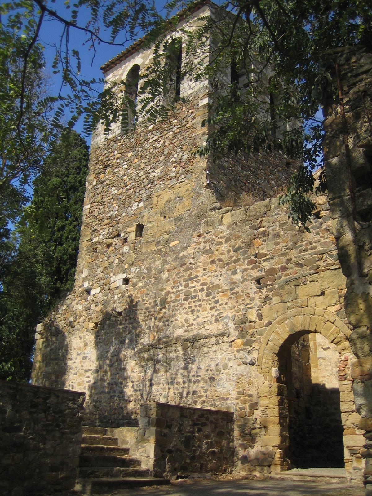 La imatge mostra la façana del monestir. Veiem a l'extrem esquerra la torre campanar i a la part inferior la porta adovellada d'accés a l'església. El sostre de la nau va caure durant el terratrèmol del segle XVI per la qual cosa l'interior de l'església es troba més enretirada. El temple és d'estil romànic benedictí i per la decoració dels absis amb els nervis i les dobles arcuacions es diu que es de tradició llombarda. És un temple molt important pels objectes artístics que s'hi van trobar com també perquè conté un dels pocs frescos d'època romànica conservats in situ.